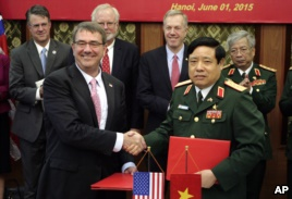 U.S. Defense Secretary Ash Carter, front  left, shakes hands with his Vietnamese counterpart Gen. Phung Quang Thanh, front right, after the two signed a joint vision statement between the two defense ministries in Hanoi, Vietnam Monday, June 1, 2015. (AP Photo/Tran Van Minh)