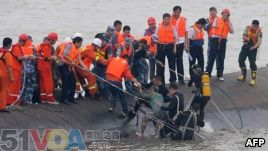 A 65-year-old woman, center, is rescued by divers from the Dongfangzhixing or