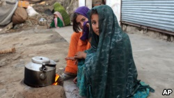 Internally displaced girls warm up by a stove after their family left their village in the Achin district of Afghanistan.