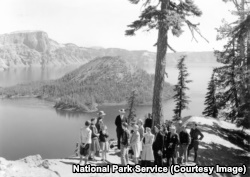 A park ranger speaks with visitors in the early days of Crater Lake National Park