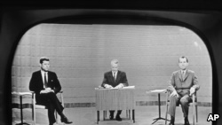 In this Sept. 26, 1960 file photo, moderator Howard K. Smith sits between, Sen. John Kennedy, left, and Vice President Richard Nixon as they appear on television studio monitor set during their debate in Chicago.