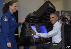 President Barack Obama sits in a flight simulator during a tour of projects at the White House Frontiers Conference at University of Pittsburgh in Pittsburgh, Oct. 13, 2016, as NASA astronaut Dr. Serena Aunon-Chancellor, left, watches.