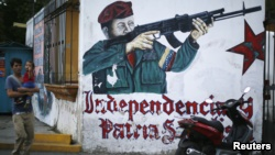 A man walks past a mural depicting Venezuelan President Hugo Chavez near his mausoleum in Caracas March 5, 2015.