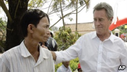 In this Saturday, March 15My Lai Massacre survivor Do Ba, left, stands with former U.S. Army officer Lawrence Colburn, right, in this 2008 picture.