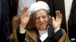 In this Dec. 21, 2015 file photo, former Iranian President Akbar Hashemi Rafsanjani waves to journalists as he registers his candidacy for the elections of the Experts Assembly, in Tehran, Iran. (AP Photo/Ebrahim Noroozi, File)